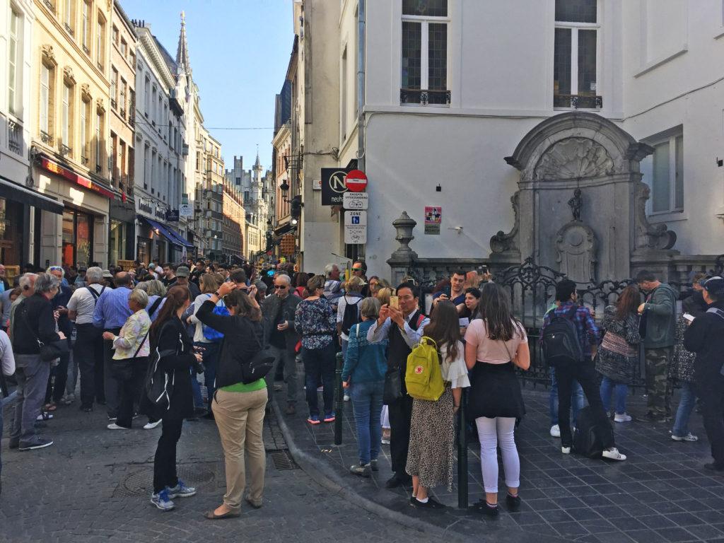 Толпа людей вокруг писающего мальчика в Брюсселе в Бельгии